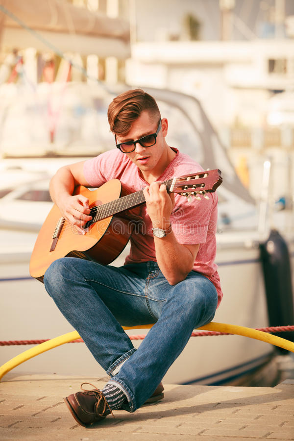 Trendy guy with guitar outdoor. Performance and show time. Young fashionable man wearing sunglasses playing classic guitar outdoor royalty free stock photos