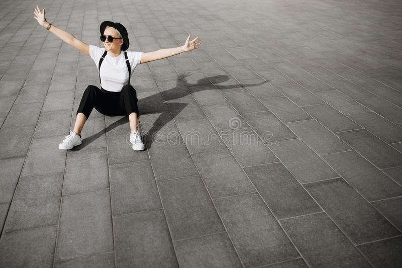 Trendy happy hipster girl with hat and sunglasses have fun sitting on the floor. Copy space area. Freedom concept. royalty free stock photo