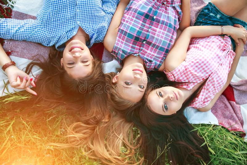 Trendy Hipster Girls Relaxing on the Grass . Summer lifestyle portrait of three hipster women laying on the grass enjoy nice day,. royalty free stock photography