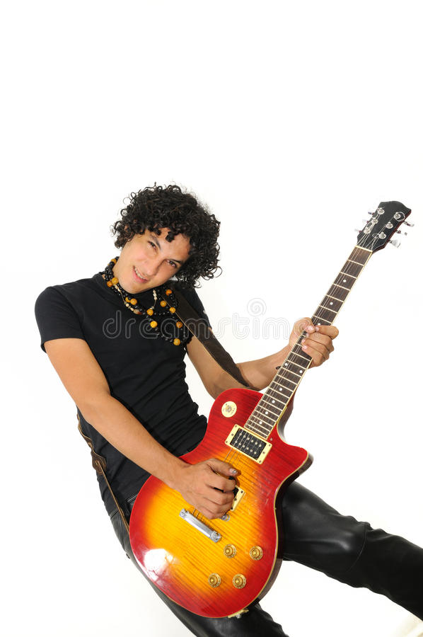 Trendy hispanic guy playing electric guitar. Portrait of trendy teen boy playing electric guitar with attitude - isolated stock photography