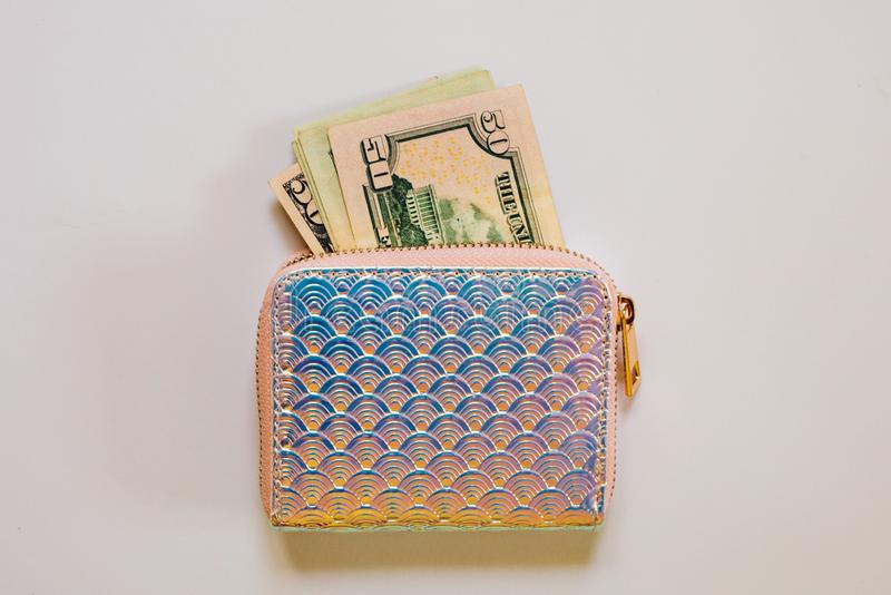 Trendy holographic purse with dollar banknotes on white background. royalty free stock photo