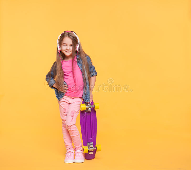 Trendy little girl child listening to music in headphones stock photography