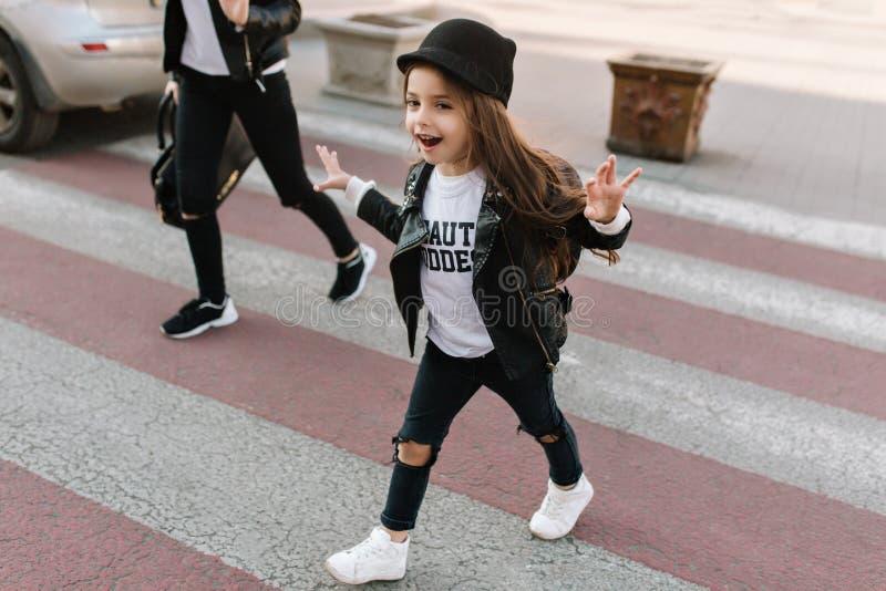 Trendy little schoolgirl walks along the pedestrian crossing after school in good mood. Portrait of joyful kid with long stock photography
