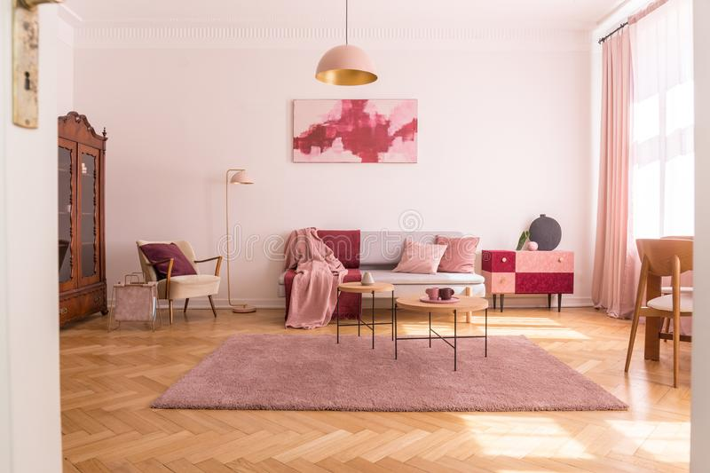 Trendy living room interior with grey couch with pastel pink pillows and blanket, stylish beige armchair with burgundy pillow and. Retro cabinet in the corner royalty free stock images