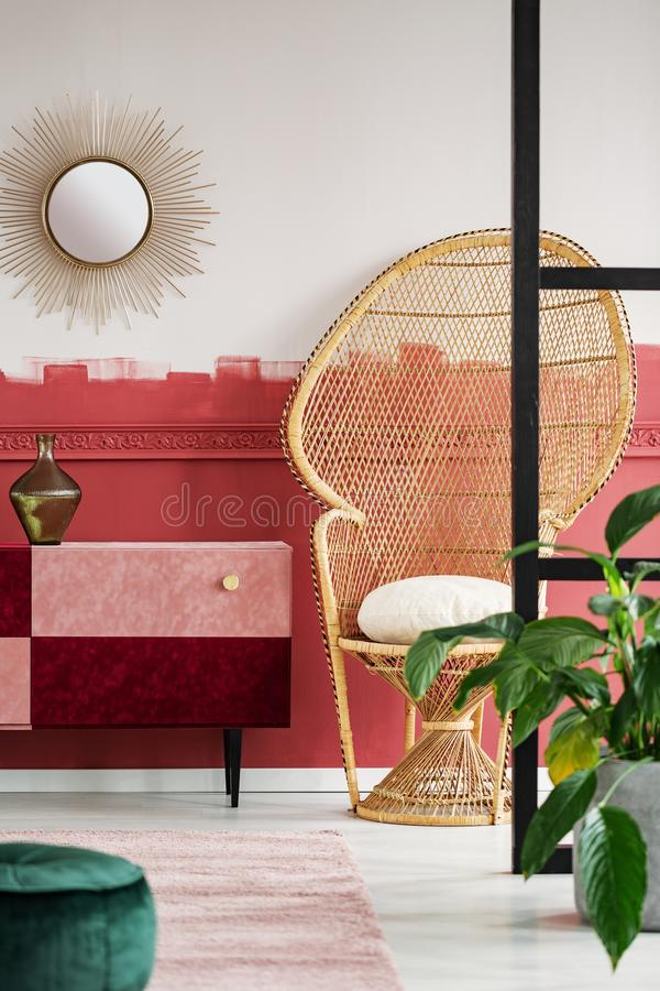 Trendy living room interior with peacock chair and handmade pastel pink and burgundy chest of drawers. Trendy living room interior with wicker peacock chair and royalty free stock photography