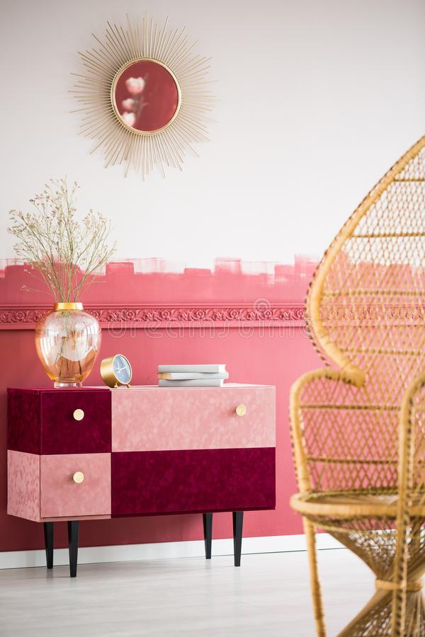 Trendy living room interior with wicker peacock chair and handmade pastel pink and burgundy chest of drawers. Trendy living room interior with wicker peacock royalty free stock photos