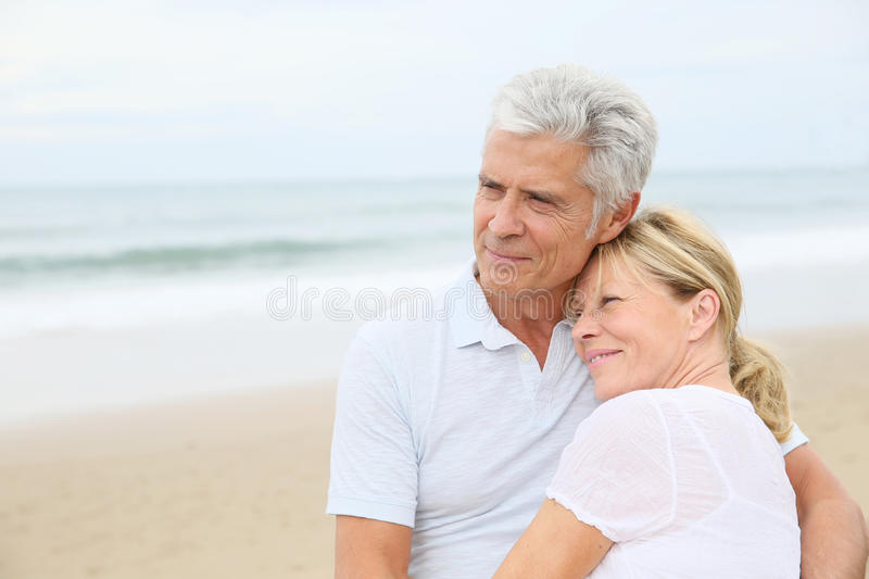 Trendy loving senior couple on the beach. In love senior couple embracing at the beach royalty free stock images