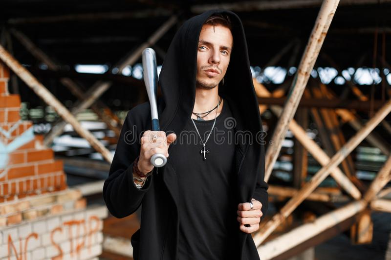 Trendy man with a hood holds a bat on the background of the old. Buildings royalty free stock images