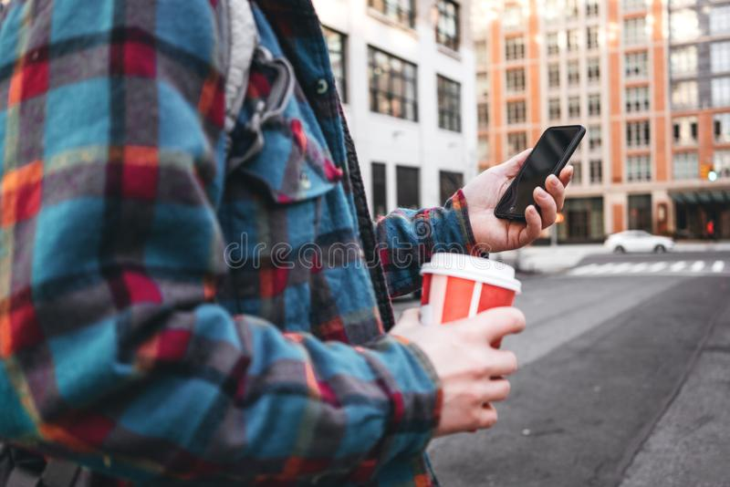 Trendy man walking through big city street with cup of hot coffee and using smartphone for video link with his friends stock image