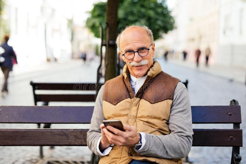 Trendy mature guy using smartphone on public bench street city stock photography