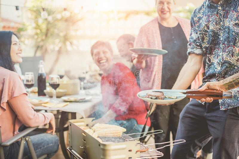 Trendy man cooking and serving meat at barbecue dinner outdoor - Chef grilling food for family friends at bbq meal outside -. Trendy men cooking and serving meat stock photo