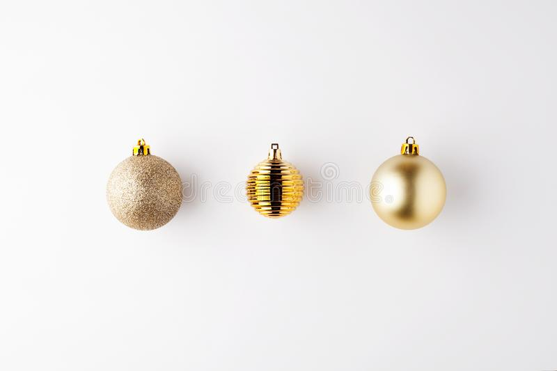 Trendy metallic gold Christmas shiny and matte balls on wite background with copy space. New Year greeting card.Minimal christmas concept idea.Flat lay,top view royalty free stock images
