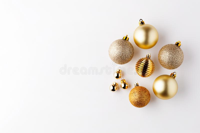 Trendy metallic gold Christmas shiny and matte balls on wite background with copy space. New Year greeting card.Minimal christmas concept idea.Flat lay,top view royalty free stock image