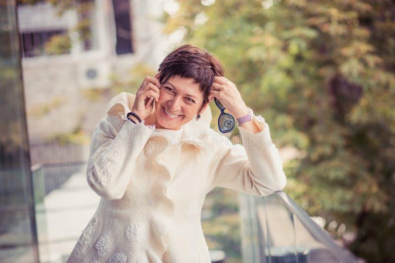 Stylish aged woman speaking on phone on street stock photo
