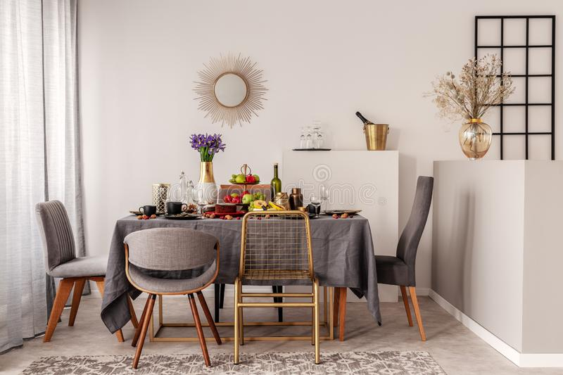 Trendy mirror in golden frame on white wall of elegant dining room stock photography
