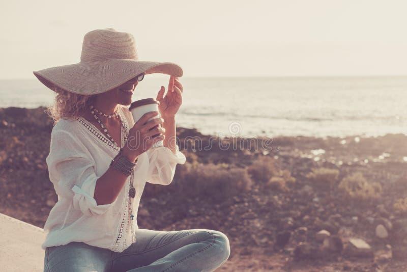 Trendy Mode fröhlich schöne, warkasische Frau mit eleganten Hut genießen Getränk im Freien Freizeit-Aktivitäten mit Strand und Oz lizenzfreie stockfotos