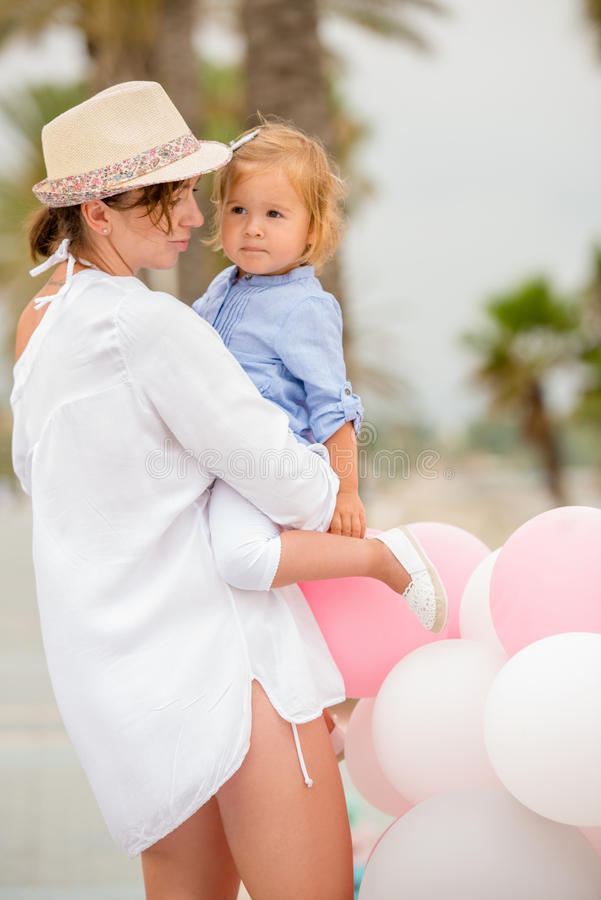 Trendy mother with a baby daughter. At a childs outdoor birthday party with pink and white balloons tropical seaside setting royalty free stock images