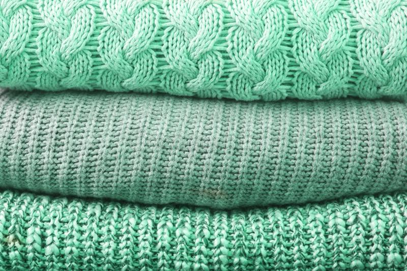 Trendy neo mint tissue clothes texture. Close up of sweaters stack. royalty free stock photo