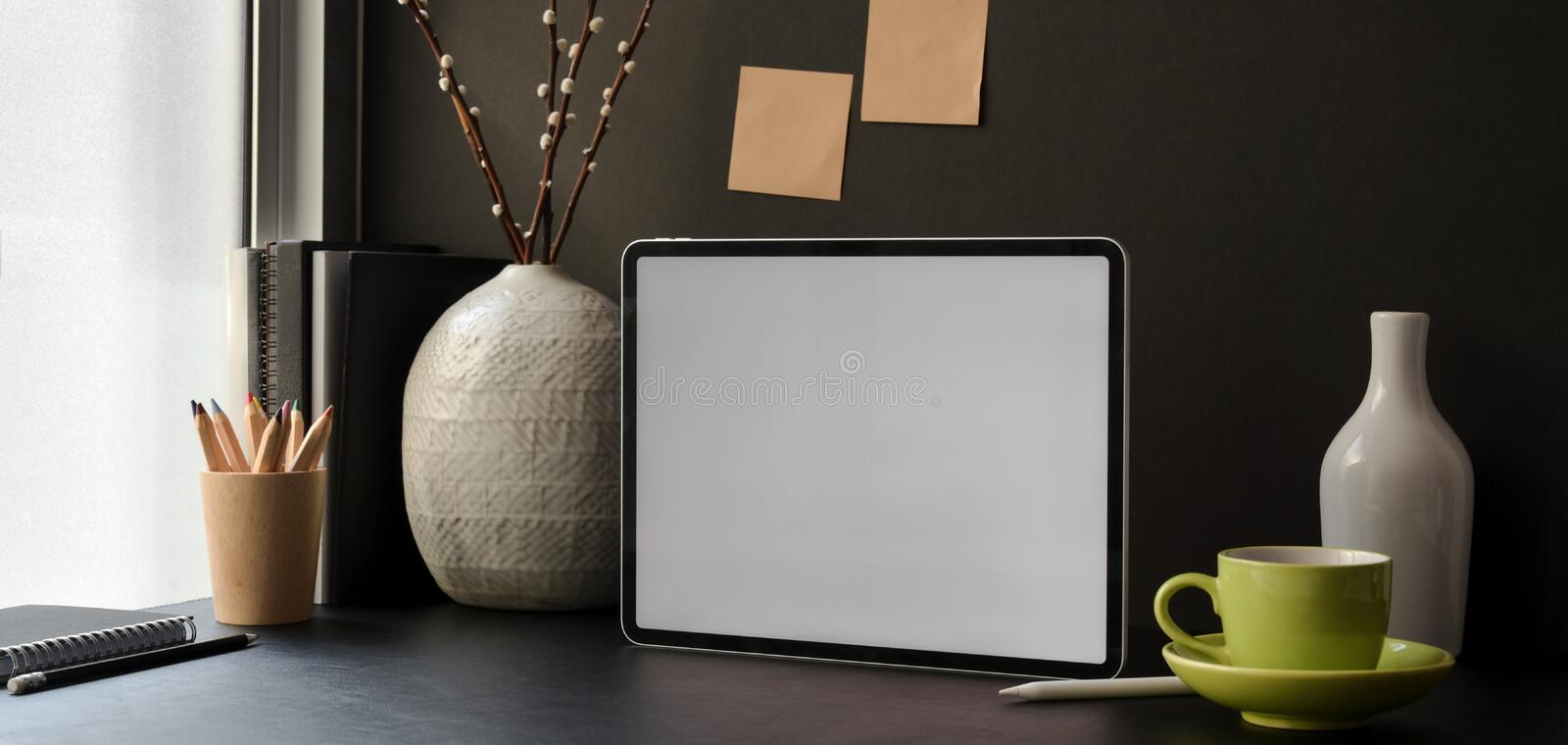 Trendy office room with blank screen digital tablet with office supplies. And decorations royalty free stock photo