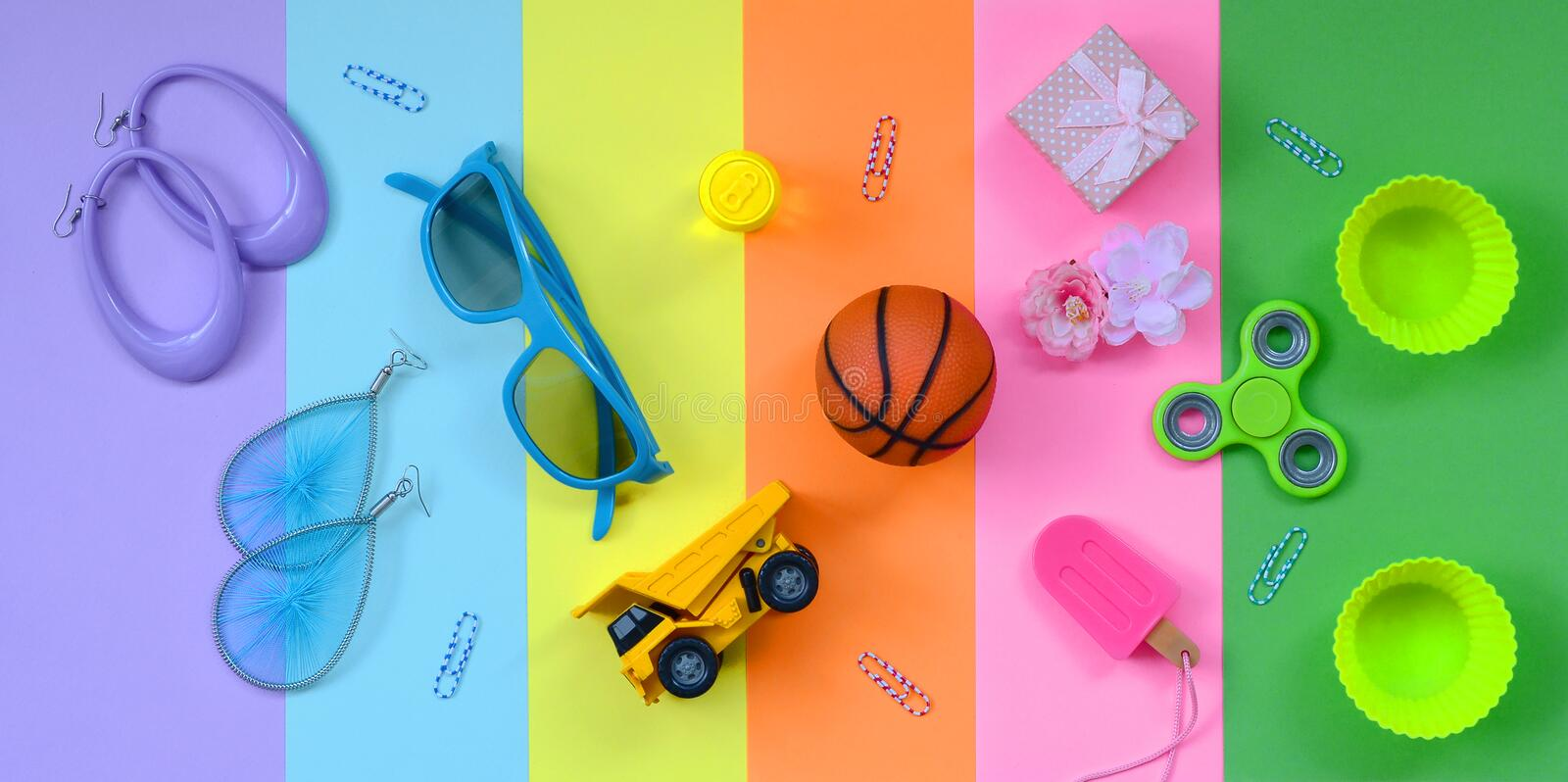 Trendy pastel composition with earrings, sunglasses, beverage can, basketball ball, toy truck, gift box, ice cream, flower and. Spinner on pink, violet, green stock image
