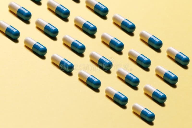Trendy pattern made with Pharmaceutical Medicinal Pillen, Tabletten und Kapseln on hell-gelb background stockbild