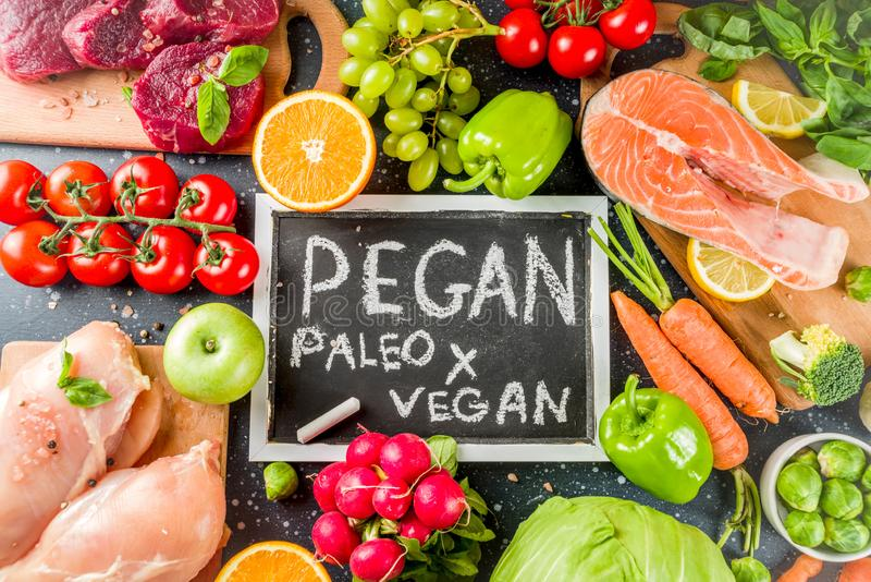 Trendy pegan diet. Vegan plus paleo diet food concept, many fresh vegetables, fruits, raw beef and chicken meat, salmon fish, dark blue background top view stock images