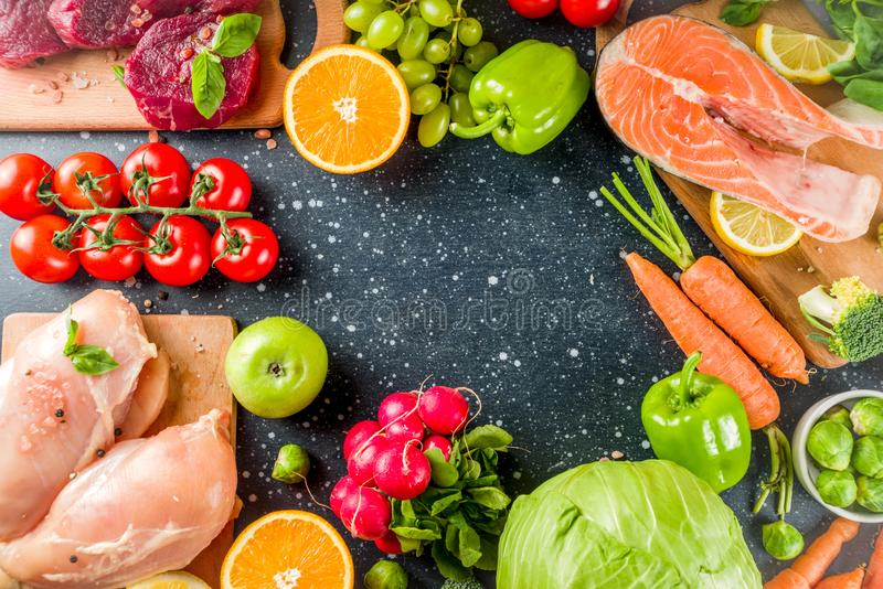 Trendy pegan diet. Vegan plus paleo diet food concept, many fresh vegetables, fruits, raw beef and chicken meat, salmon fish, dark blue background top view royalty free stock images