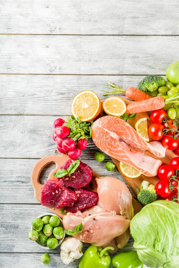 Trendy pegan diet. Vegan plus paleo diet food concept, many fresh vegetables, fruits, raw beef and chicken meat, salmon fish, white wooden background top view royalty free stock photos