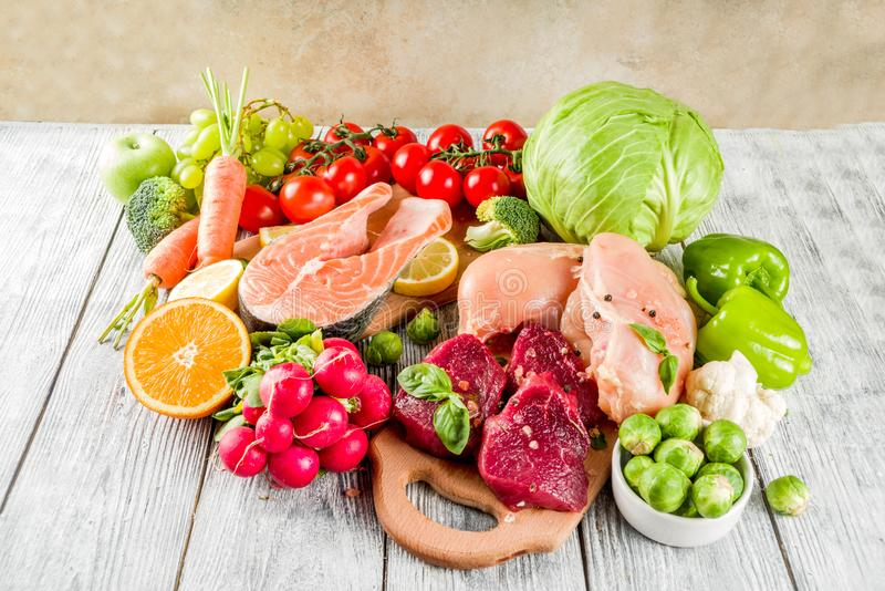 Trendy pegan diet. Vegan plus paleo diet food concept, many fresh vegetables, fruits, raw beef and chicken meat, salmon fish, white wooden background top view royalty free stock images