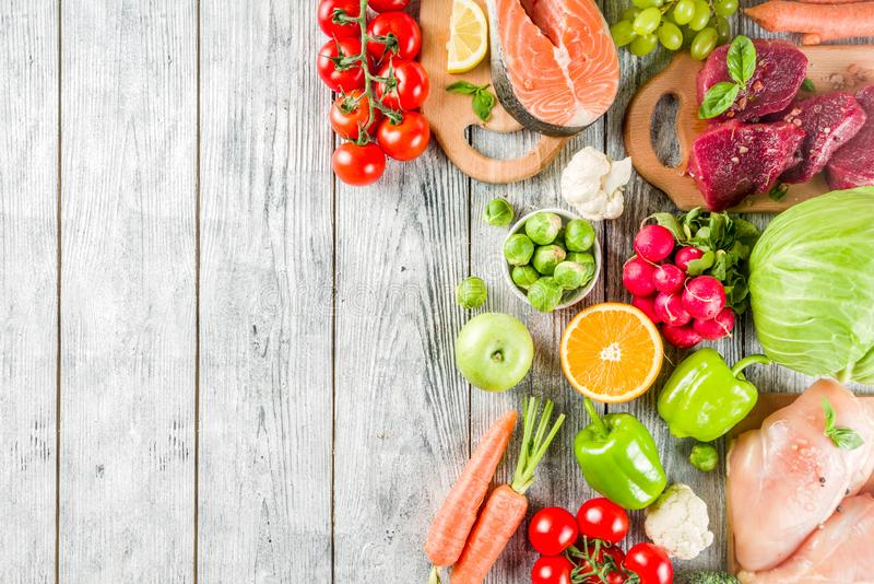Trendy pegan diet. Vegan plus paleo diet food concept, many fresh vegetables, fruits, raw beef and chicken meat, salmon fish, white wooden background top view royalty free stock photography