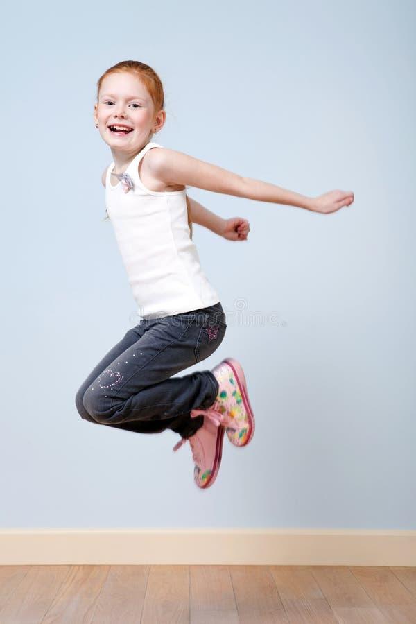 Trendy roodharig meisje dat binnen springt royalty-vrije stock afbeelding