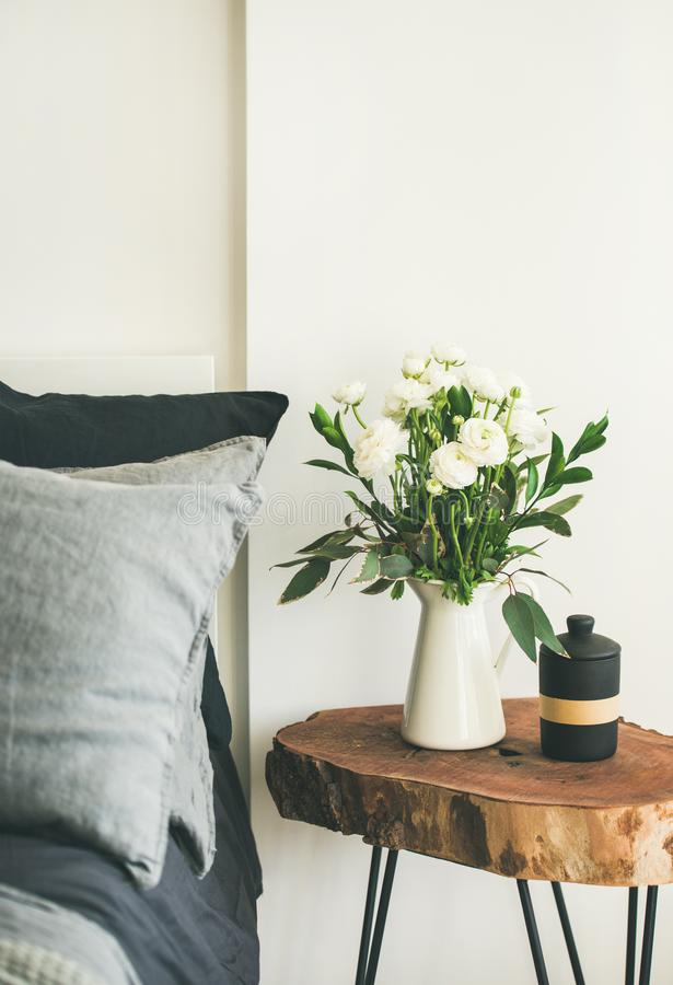 Trendy Scandinavian style bedroom interior. Trendy Scandinavian style interior shot. Bedroom with washed linen grey pillows and wooden nightstand with bucket of royalty free stock photo