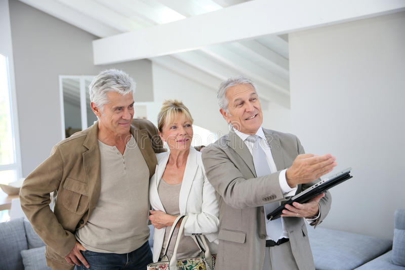Trendy senior couple buying new house with real estate agent stock image