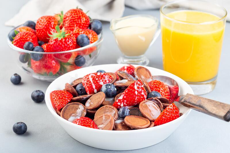 Trendy small chocolate cereal pancakes served with condensed milk, strawberry, blueberry and orange juice, in a white bowl, stock images