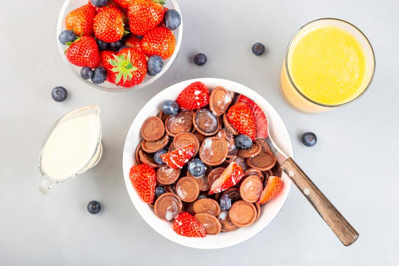 Trendy small chocolate cereal pancakes served with condensed milk, strawberry, blueberry and orange juice, in white bowl, stock images