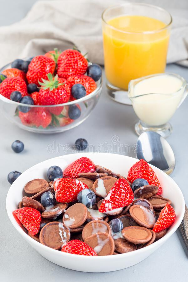 Trendy small chocolate cereal pancakes served with condensed milk, strawberry, blueberry and orange juice, in white bowl, vertical stock image