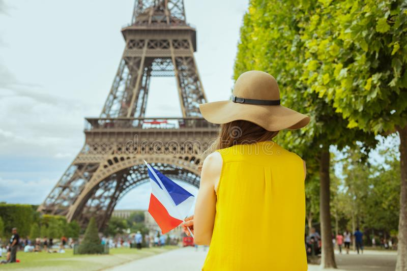 Trendy solo traveller woman with French flag in Paris, France. Seen from behind trendy solo traveller woman in yellow blouse and hat with French flag in Paris stock image