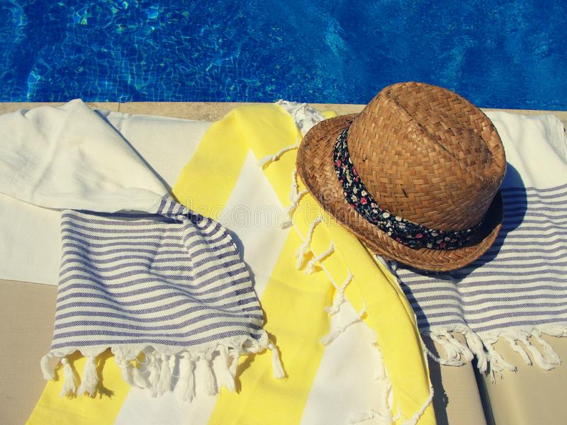 Trendy straw hat with ribbon and cotton towels on a sunbed near the swimming pool. Filtered image, vintage filter effect royalty free stock photo