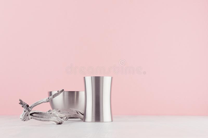 Trendy stylish home decor  with elegant silver polished abstract decoration and old shabby snag on white wood shelf and soft light. Pink background stock image