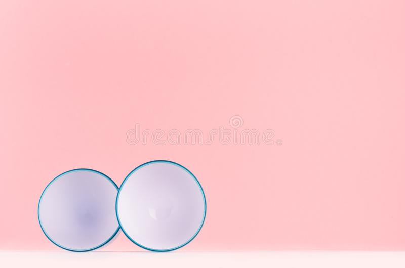Trendy stylish home decor with elegant white abstract rounded plastic decoration with blue rim  on white wood shelf and pink light. Trendy stylish home decor royalty free stock images