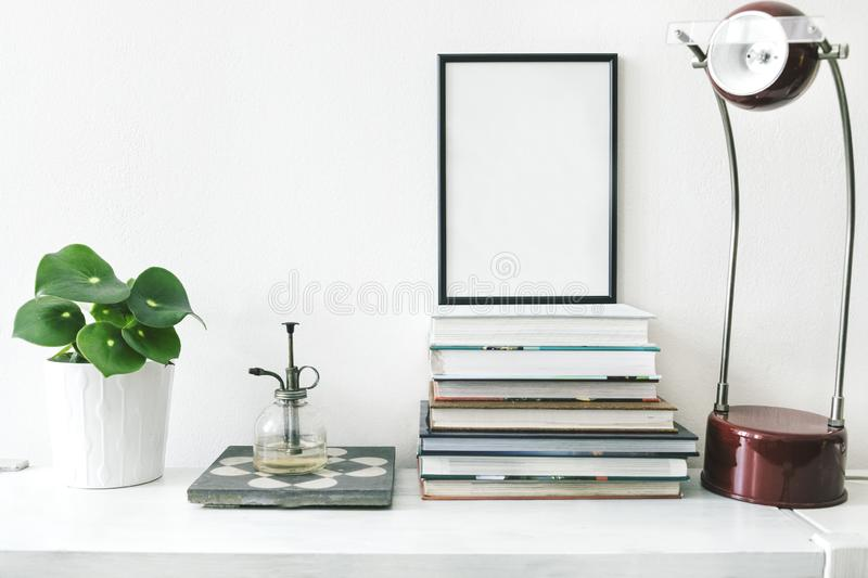 Trendy and stylish interior of living room with mock up poster frame ,plants and vintage accessories on the wooden shelf. White royalty free stock photo