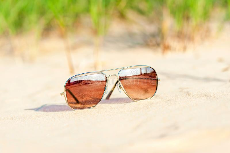 Trendy sunglasses lost on the beach sand. Multicolored outdoors stock images