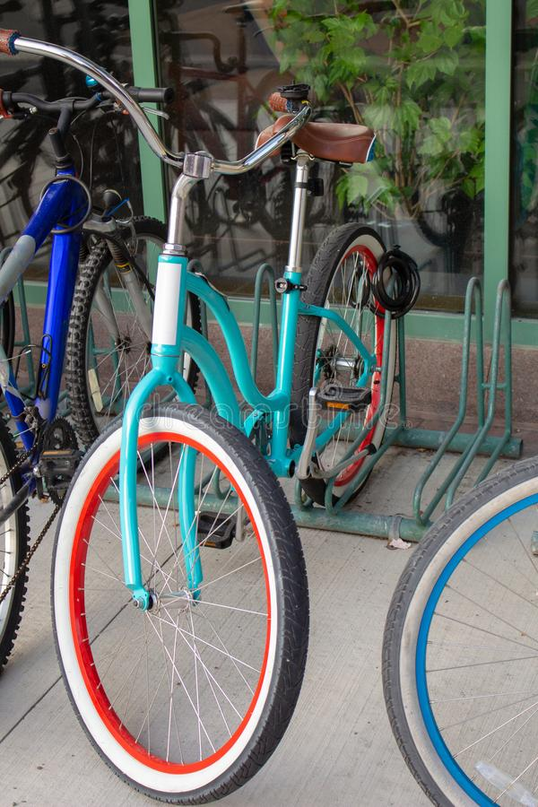 A Trendy Teal Bicycle on an Outdoor Bike Rack royalty free stock images
