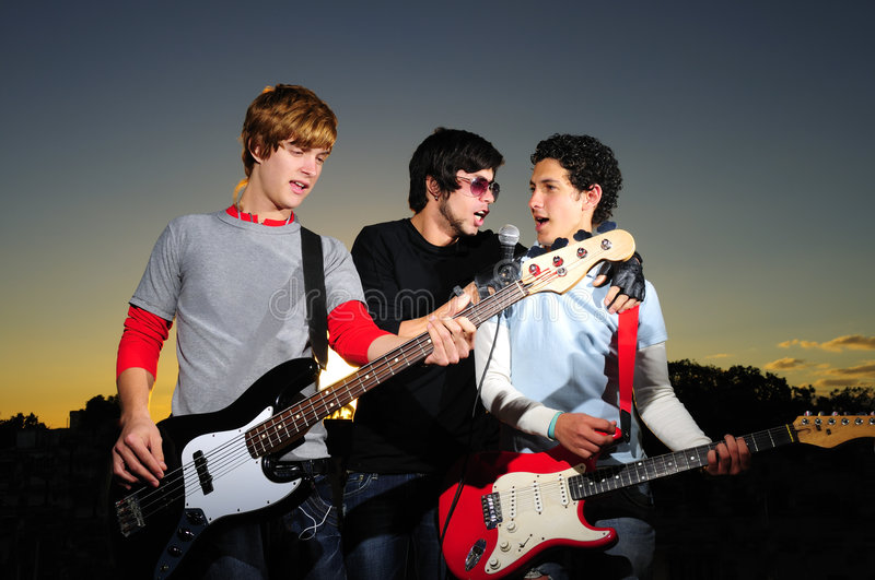 Trendy team of musicians. Portrait of three trendy teenagers playing music outdoors stock photos