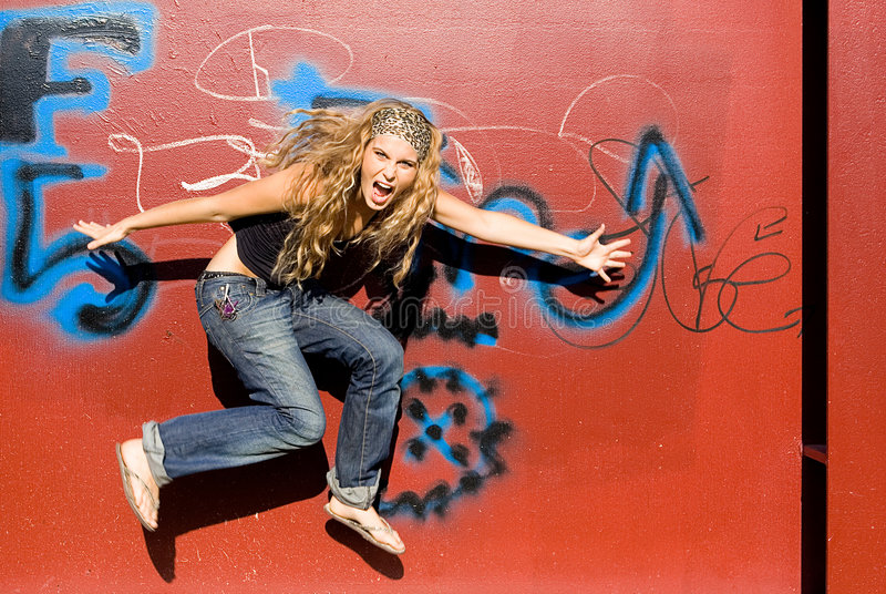 Trendy teenager jumping royalty free stock images