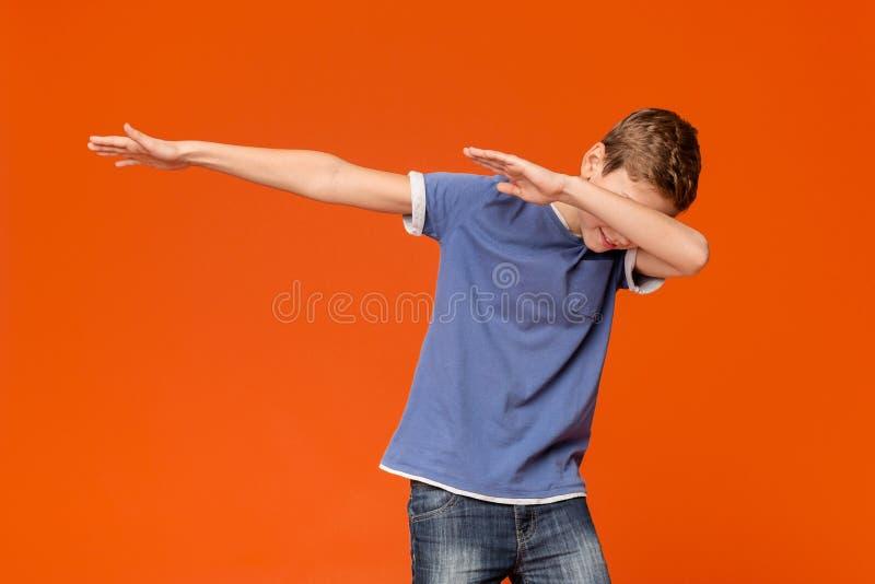 Trendy teenager making dab gesture, having fun. On orange studio background royalty free stock photos