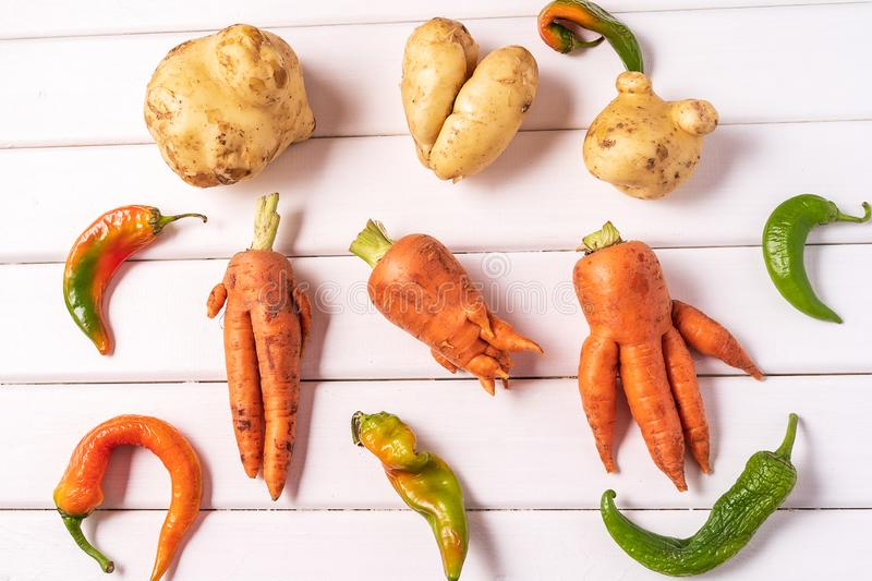 Trendy ugly curved vegetables - potato, carrot and chilli pepper on white wooden background stock photography