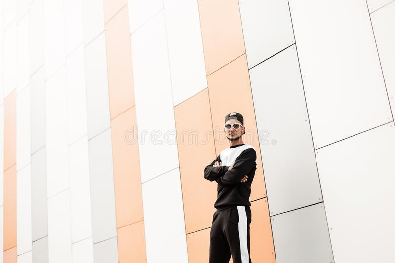 Trendy urban young hipster man in stylish cap in sunglasses in fashionable black sports suit is standing near a modern building. In the city on a bright sunny stock photos