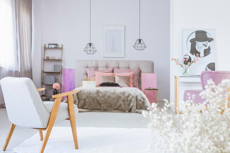 Vintage armchair in cute bedroom interior with black and white poster and king size bed with satin bedding royalty free stock photography