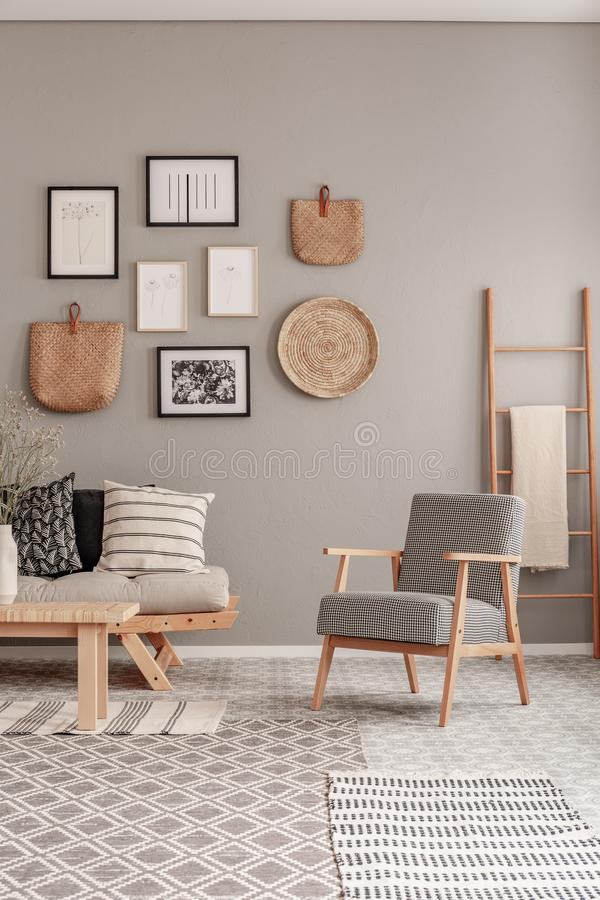 Trendy vintage armchair next to chic scandinavian sofa with pillows in classy living room interior.  stock photography
